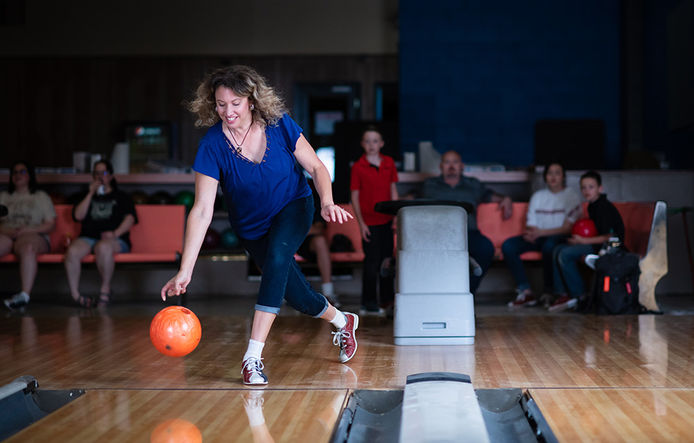 Woman bowling with friends watching behind