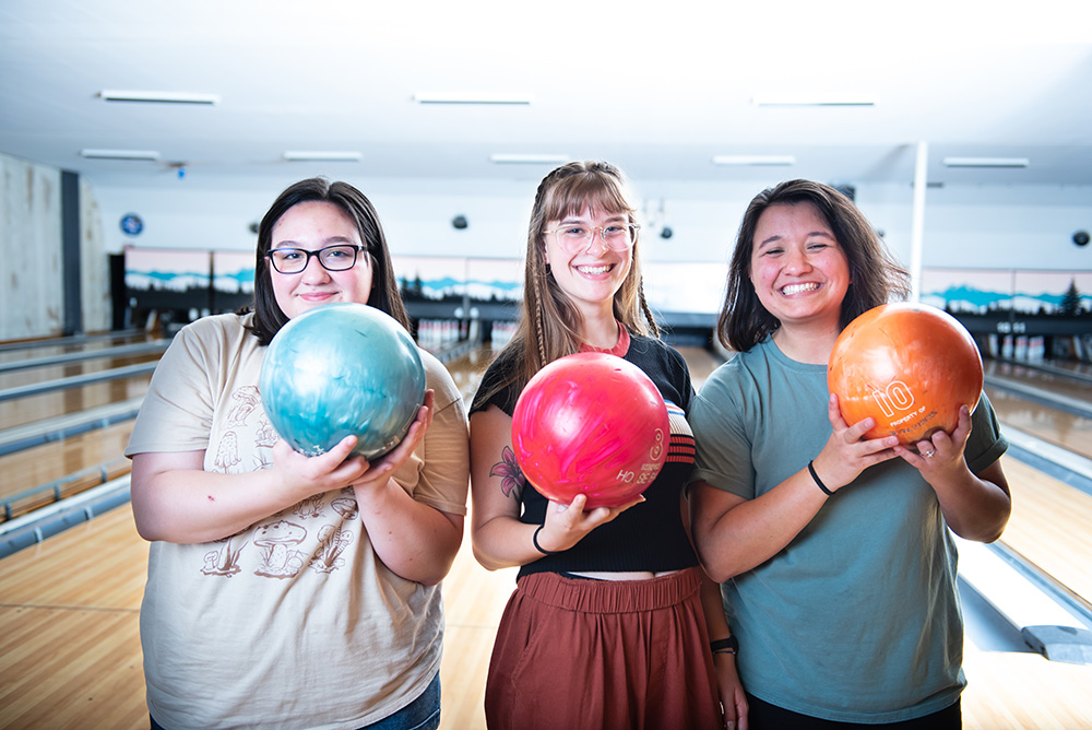 Three teen girls holding bowling balls